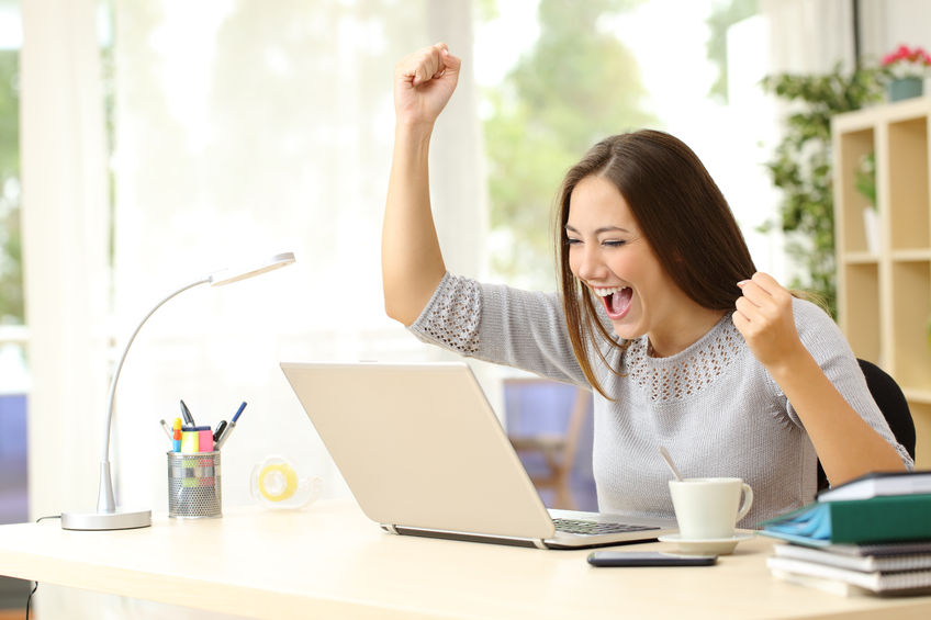 50532398 – euphoric winner watching a laptop on a desk winning at home